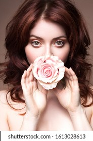 Portrait Beautiful girl with flower. Beauty portrait of seductive young woman with perfect healthy skin and natural makeup