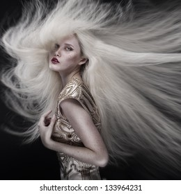 Portrait of a beautiful girl with flying blond hair isolated on black background