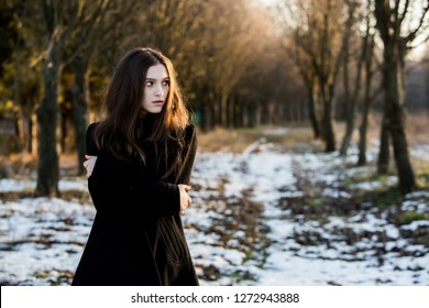 Portrait of a beautiful girl with flying hair in the wind. Young sad woman. Portrait of lonely woman