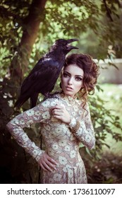 Portrait of a beautiful girl in the forest with a raven on her shoulder. Fashio photo shoot of a model in the summer in the park. tame black bird, wild raven with a girl