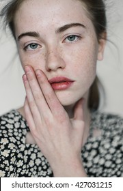 portrait of a beautiful girl with freckles close-up