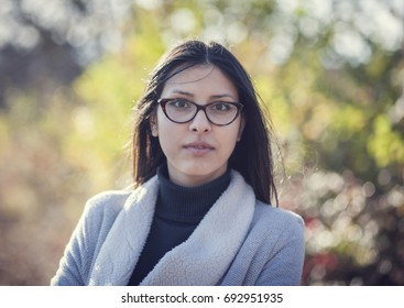 Portrait of a beautiful girl in glasses in autumn park