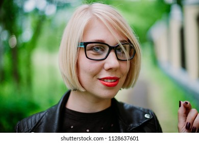 Portrait of a beautiful girl in glasses. Green park background with blur