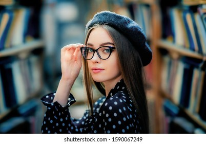 Portrait of a beautiful girl with glasses in library.