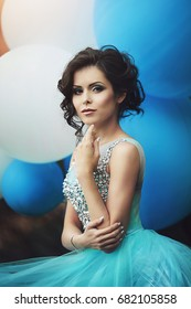 Portrait of a beautiful girl graduate in a blue dress with big blue and white balloons. Elegant young woman in a beautiful dress in the park. Art photo.