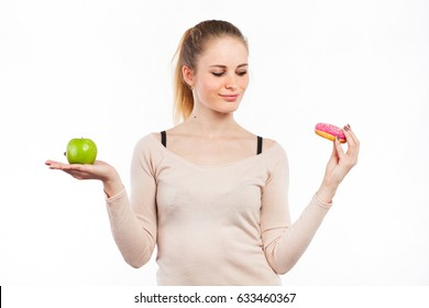 Portrait of a beautiful girl with a green apple and a donut, isolated on white