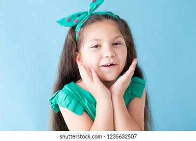 Portrait of a beautiful girl in a green dress on a blue background