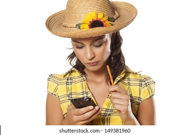 portrait of a beautiful girl with hat eating grissini and thoughtfully reading text message on her phone