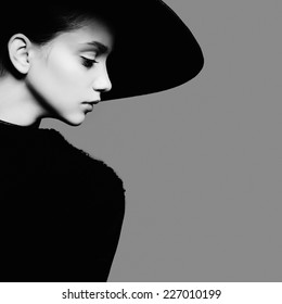 Portrait of beautiful girl in hat in profile, posing in studio, black and white photography
