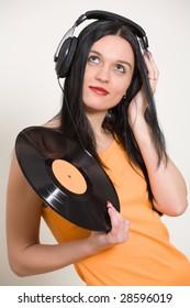 Portrait of the beautiful girl in headphones with vinyl