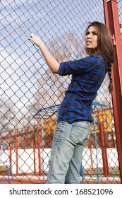 Portrait of a beautiful girl hipster. Trendy young naughty woman holding at the net. Outdoors, lifestyle.
