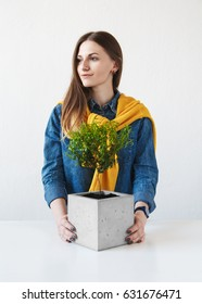 Portrait of a beautiful girl with a houseplant in a concrete pot