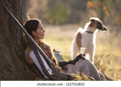 Portrait of a beautiful girl - a hunter with dogs, Russian greyhound