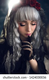 portrait of a beautiful girl in the image of the Japanese lolita. girl in a black dress and with silver hair. anime style