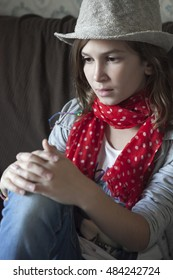 Portrait of beautiful girl in jeans wearing hat and red scarf sitting on the sofa and thinking