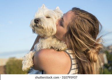 A portrait of beautiful girl keeping pretty white West Highland dog outdoor