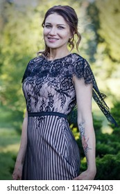Portrait of a beautiful girl in a lace dress in a park.