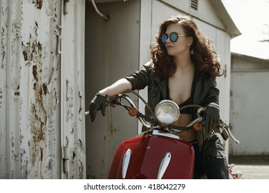 portrait of a beautiful girl in leather jacket, brassiere and glasses near red retro motorcycle