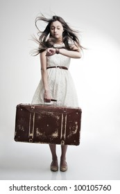 portrait of a beautiful girl with long and developing hair with a suitcase in his hand  on a white background