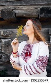 Portrait of Beautiful girl with long hair in white ethnic shirt with flower bouquet. Traditional village of Eastern Europe.
