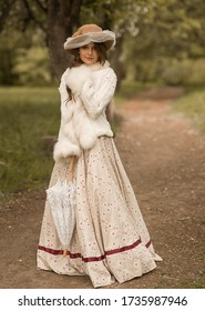 Portrait of a beautiful girl with long hair in a hat, in a long white dress, with a lace umbrella. Stands on a forest path and looks directly into the camera. Historical reconstruction - Shutterstock ID 1735987946