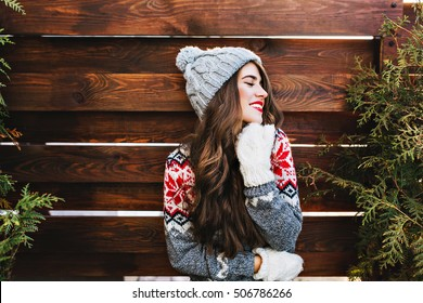 Portrait beautiful girl with long hair and red lips in warm winter clothes on wooden background. She is smiling to side and keeps eyes closed