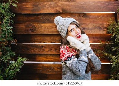 Portrait beautiful girl with long hair in knitted hat and winter sweater on wooden background. She touching face with hands in gloves and smiling to camera