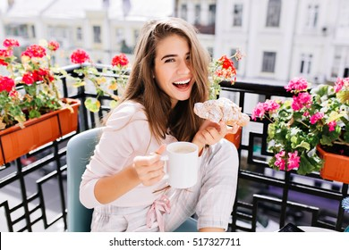 Portrait beautiful girl with long hair having breakfast on balcony in the morning in city. She holds a cup, croissant, laughing to camera