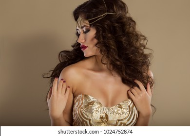 Portrait of beautiful girl with long wavy hair and fashion makeup is wearing head jewelry and golden dress, studio shoot