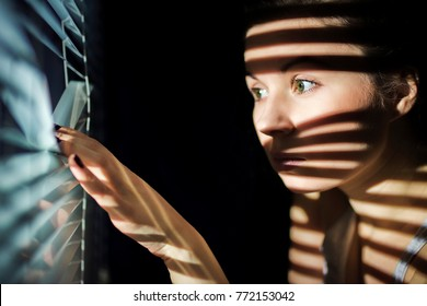 Portrait, beautiful girl, looks through blinds