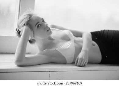Portrait of beautiful girl lying near the window in his underwear, life-style, black and white photography