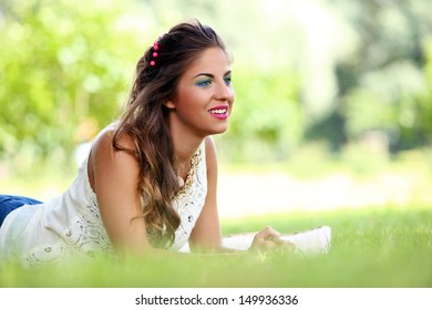 Portrait of a beautiful girl lying on a carpet in a park
