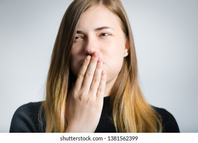 portrait of a beautiful girl nauseated and covered her mouth with her hand, studio photo over gray background