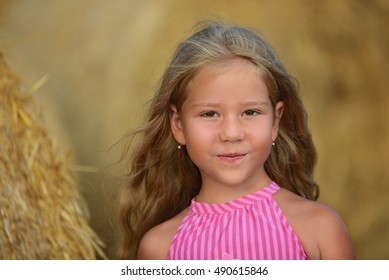 Portrait of beautiful girl near a stack of straw