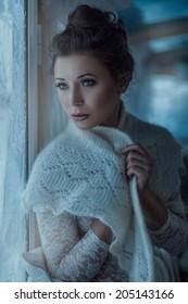 Portrait of beautiful girl near the window, her shawl.