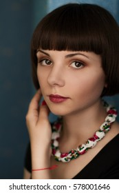 Portrait beautiful girl with necklace and hair bob hair straightens and removes the view from the camera