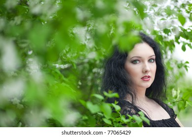 Portrait of a beautiful girl next to flowering tree