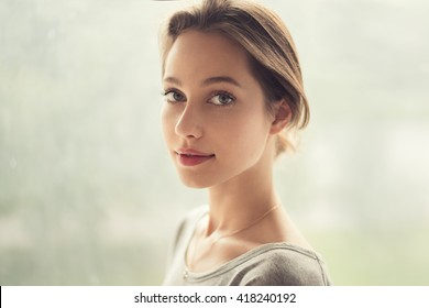 portrait of a beautiful girl on a background of a window
