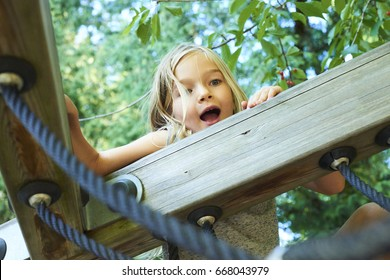 Portrait of a beautiful girl on a rope park among trees. Children summer activities.
