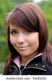portrait of the beautiful girl outdoors on the green defocused background