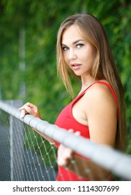 portrait of beautiful girl outdoors in red dress