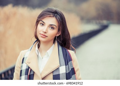 Portrait of a beautiful girl outside looking at you camera serious isolated defocused light brown background park outdoors
