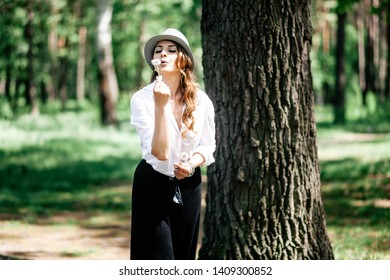 Portrait of a beautiful girl in the park with a flower. In a hat and white shirt. Cheerful mood and smile.