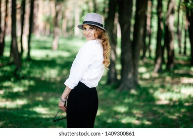 Portrait of a beautiful girl in the park. In a hat and white shirt. Cheerful mood and smile.