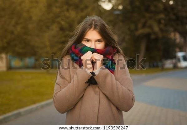 Retrato de una hermosa chica en el parque. Adolescente cubriendo la cara con bufanda de lana y abrigo marrón. Foto de cierre. Los estudiantes jóvenes se divierten. Foto de estilo de vida. bella chica helada en el parque, frío otoño