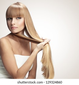 Portrait of beautiful girl with perfect long shiny blond hair studio shot