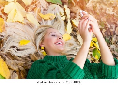 Portrait of a beautiful girl with a phone in an autumn park