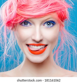 Portrait of beautiful girl with pink hair on a blue background, showing tongue