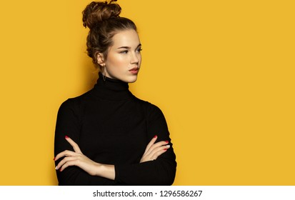 Portrait of beautiful girl posing for fashion photoshoot on yellow background. Pretty model dressed in stylish black pullover. Trend and lifestyle concept