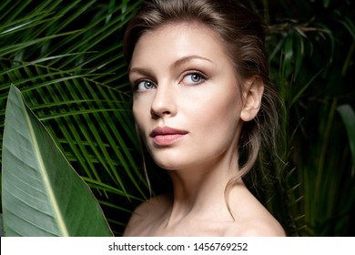 Portrait of beautiful girl posing on natural background. Lovely model with perfect and clean skin looking away with tenderness. Beauty and skincare concept